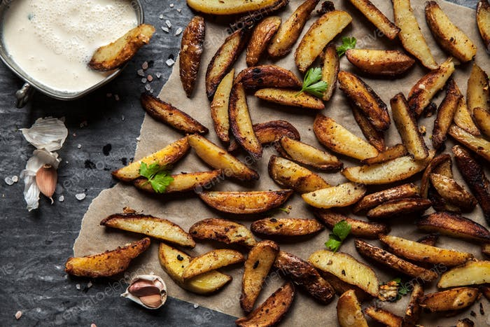 Delicious potatoes with rosemary on parchment, closeup