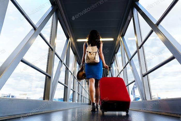 Junges Mädchen Reisenden zu Fuß mit tragen halten Koffer im Flughafen.