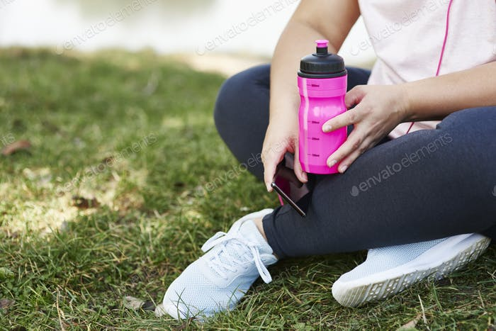 Tired woman drinking water after hard workout