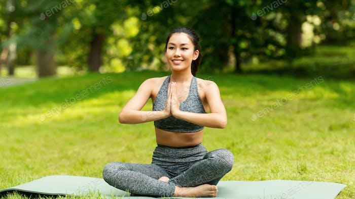 Beruhige asiatische Mädchen meditieren in Lotus-Pose während ihrer Yoga-Klasse im Freien