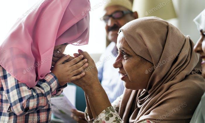 Muslim daughter kisses her mother's hands