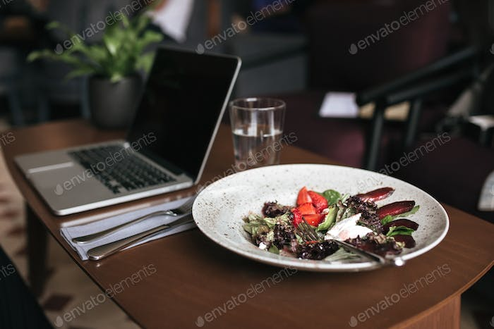 Close up photo of salad, laptop and glass of water and knife with fork on table in restaurant