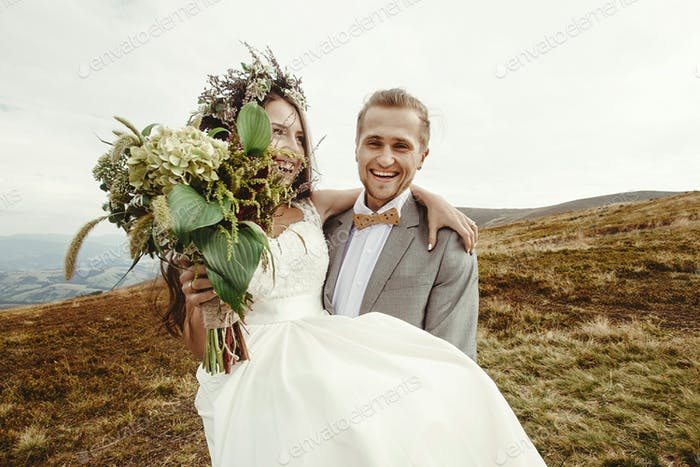 stylish groom carrying happy bride and having fun