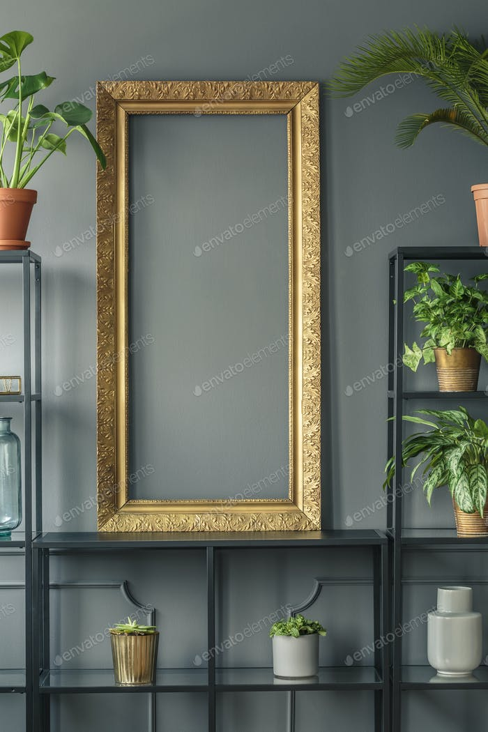 A gold frame and plants in vases on black shelves next to a grey