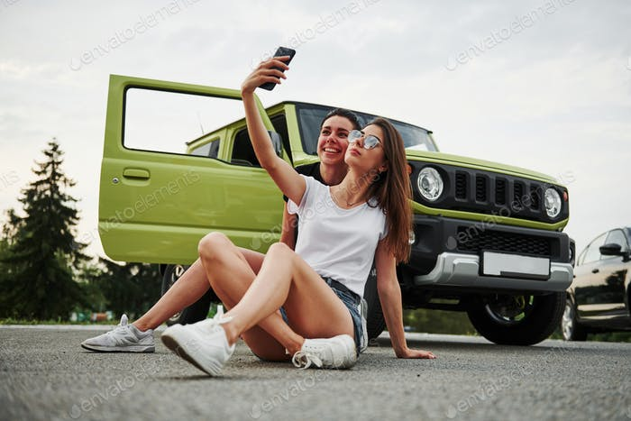 Two female friends have fun by sitting neat the new gren vehicle