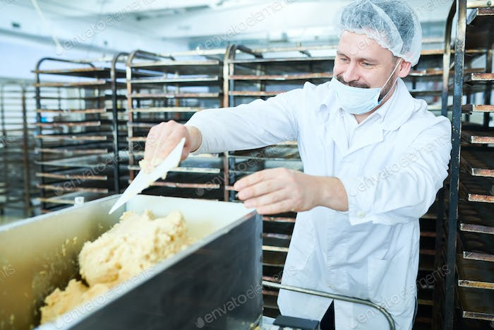 Confectioner mixing dough in factory