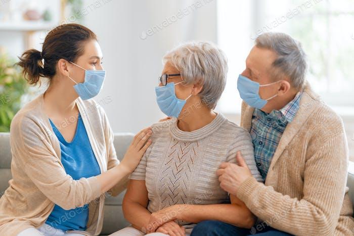 Erwachsene Tochter und ältere Eltern tragen Gesichtsmasken