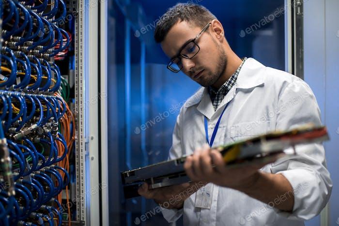 Scientist Inspecting Supercomputer Servers