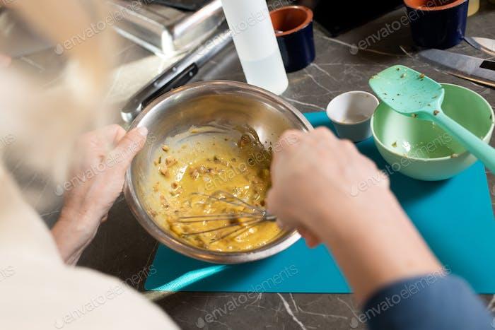 Hände reifer Frauen mischen Zutaten mit Whisker in Metallic-Schüssel nach Tisch