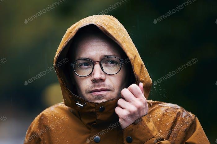 Человек в водонепроницаемый куртка во время дождя