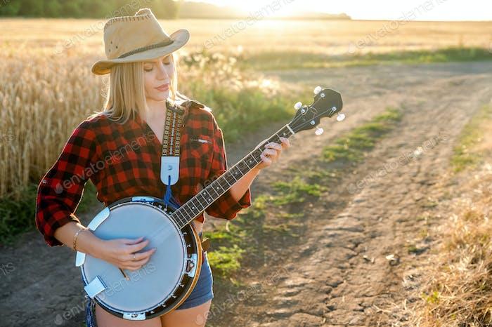 Ein Landmädchen mit einem Banjo bleibt in einem Feld