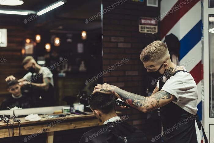 Barber shaving man in chair