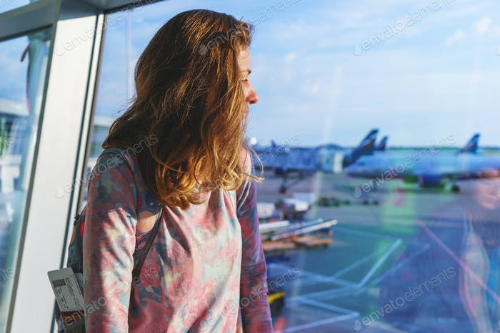 pretty young girl traveler with a backpack next to the panoramic windows of the passenger terminal