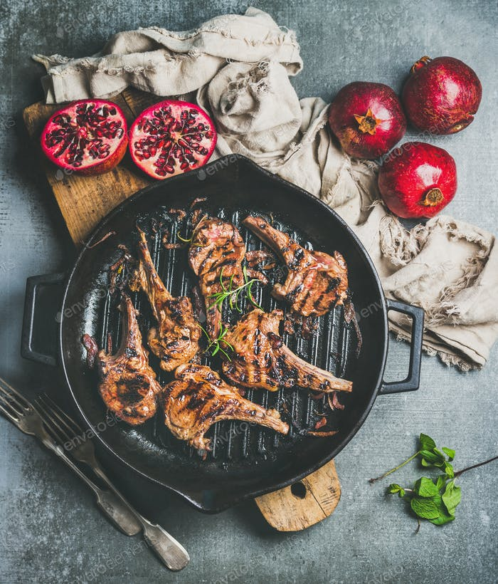 Grilled lamb meat chops served with fresh pomegranates, grey background