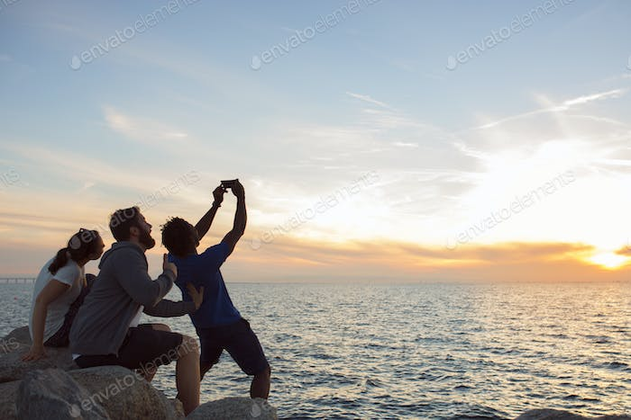 Friends taking selfie at sunset