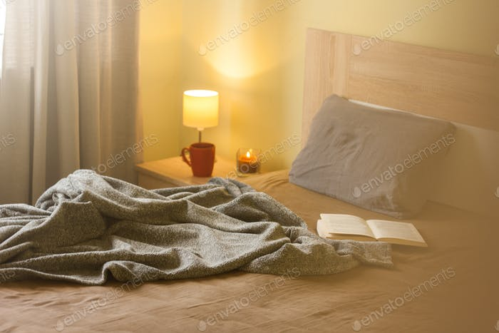 Cozy room interior, comfortable bed with soft pillow and blanket, lamp and book