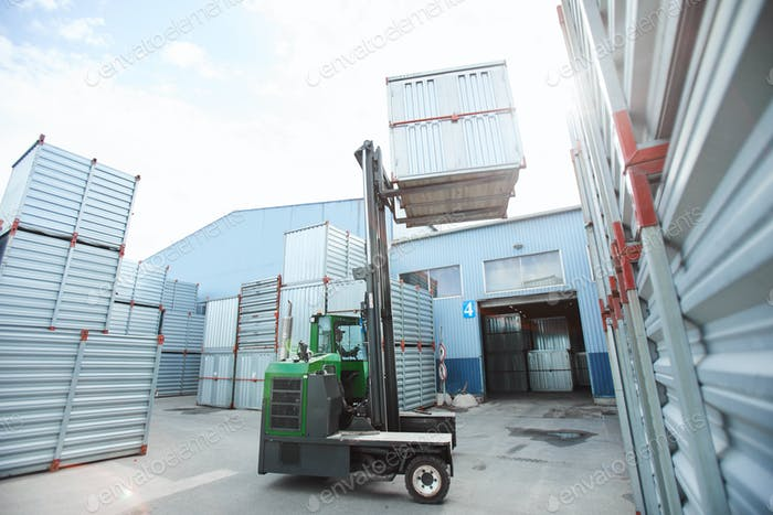 Forklift truck lifting metal container