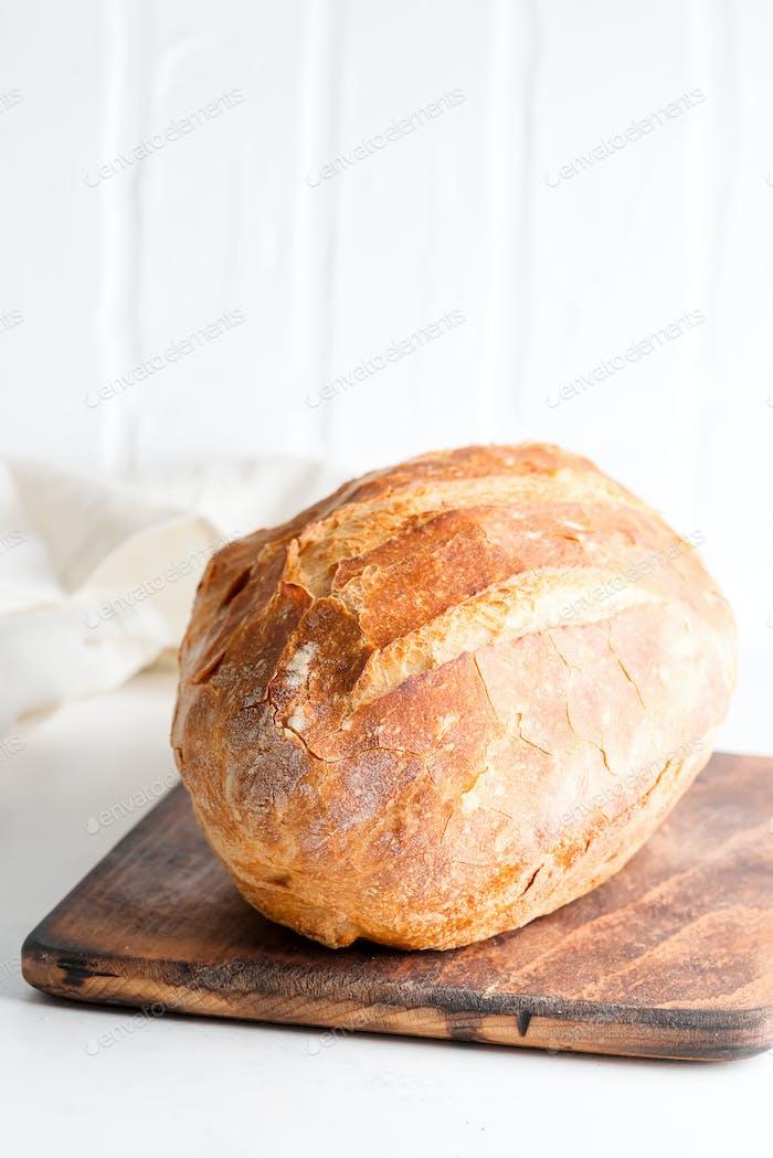 Hausgemachtes frisch gebackenes Brot auf einem Holzbrett und hellgrauem Marmortisch dekoriert Textilhandtuch