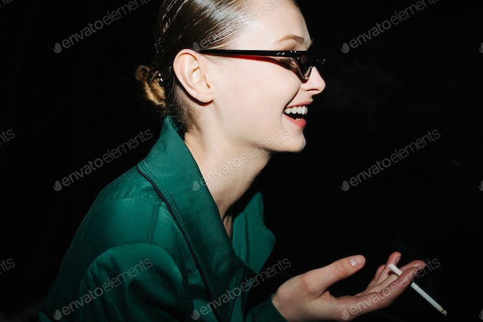 Portrait of young smiling lady in fashionable sunglasses standing and smoking at night