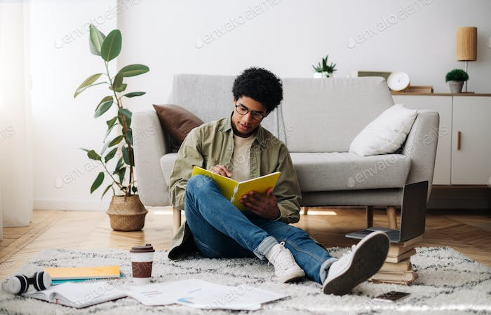 Web based education. Busy black teen guy taking notes during online lecture on laptop at home