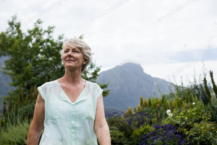 Senior woman standing in lawn