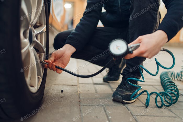 Male person checks the tire pressure, tyre service