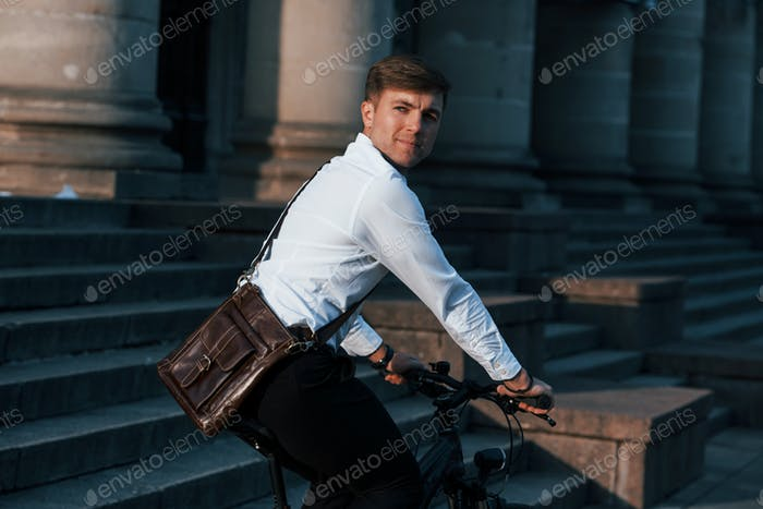 Ecological and healthy transport. Businessman in formal clothes with black bicycle is in the city
