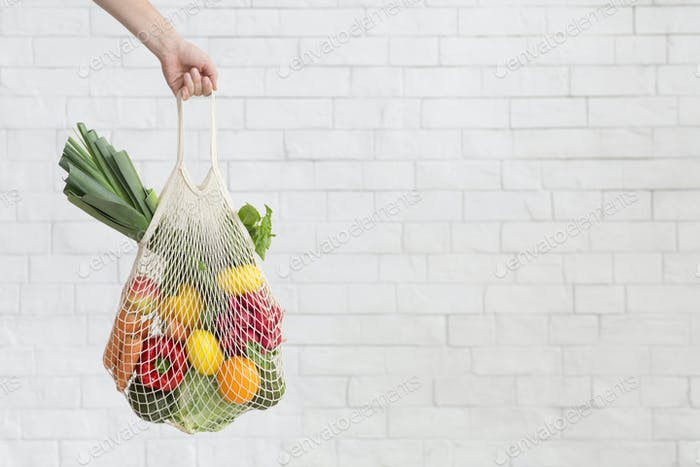 Woman holding fresh vegetables over white bricks wall in eco shopping bag