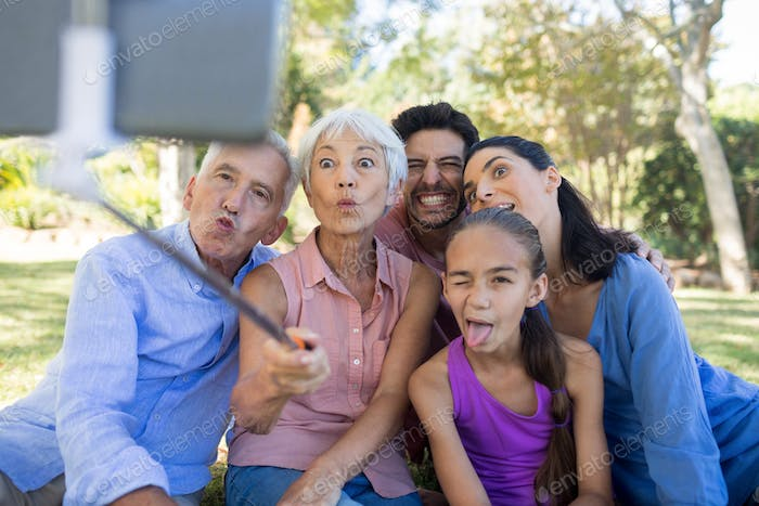 Family making funny faces while taking a selfie in the park