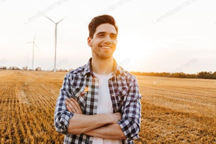 Glücklicher Mann steht gegen die Industrielandschaft
