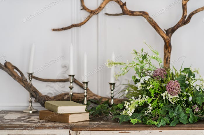 Romantic autumn scenery for photo shoots. Old books, green branch, candles