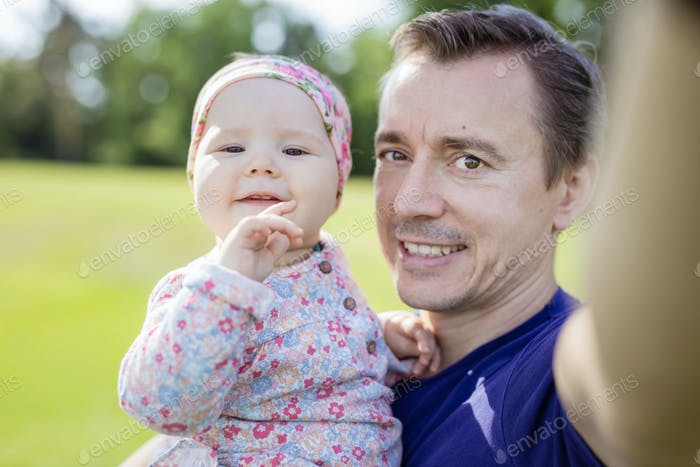 Father carrying baby daughter and taking selfie with smartphone