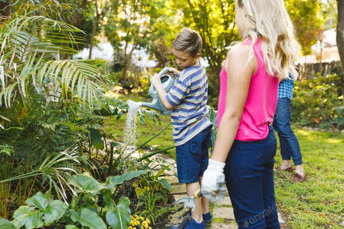 Caucasian son and daughter watering plants in garden with mother and father in background