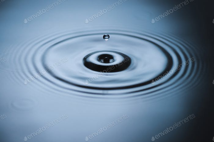 Water droplet splash on surface and leaving ripples