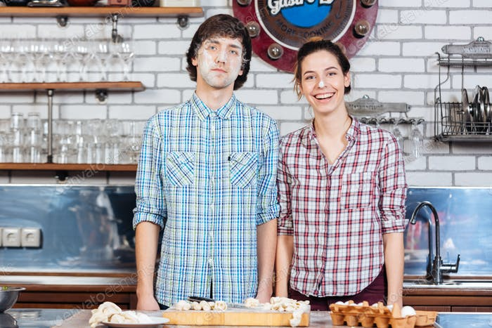 Amusing couple with flour on their faces standing in kitchen