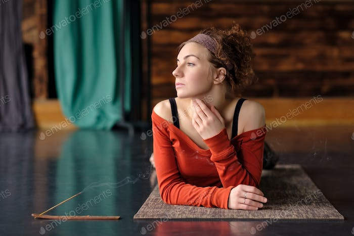 Tired young curly woman relax after training on mat.