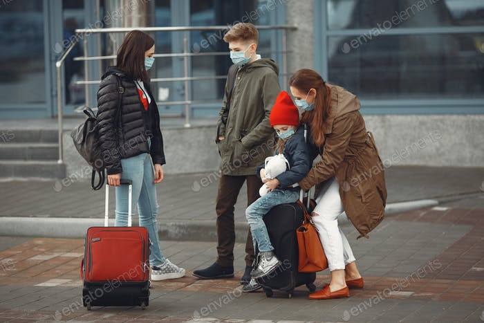 European mothers in respirators with kids are standing near a building
