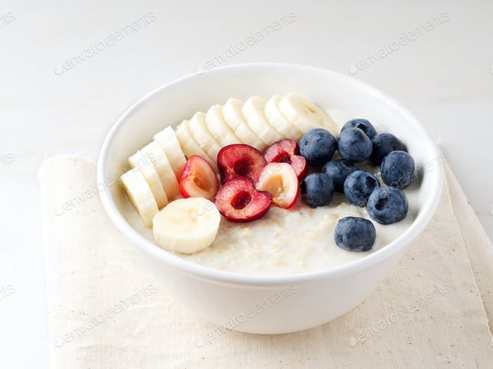 Large bowl of tasty and healthy oatmeal with fruits and berry for Breakfast, morning meal