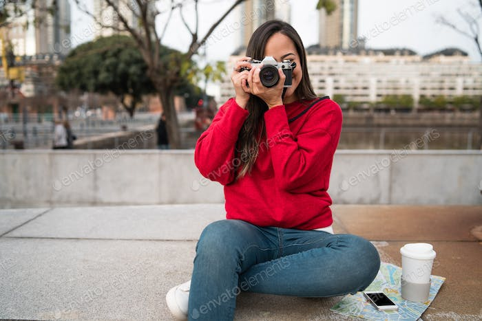 Young woman using a professional camera.