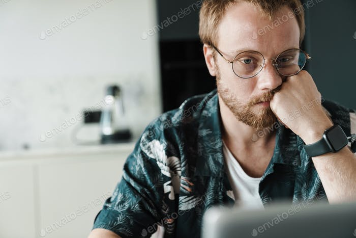 Photo of focused redhead man working with laptop and thinking