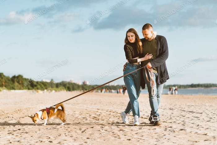 Young happy couple and dog walking on beach. Handsome man gently embracing beautiful woma
