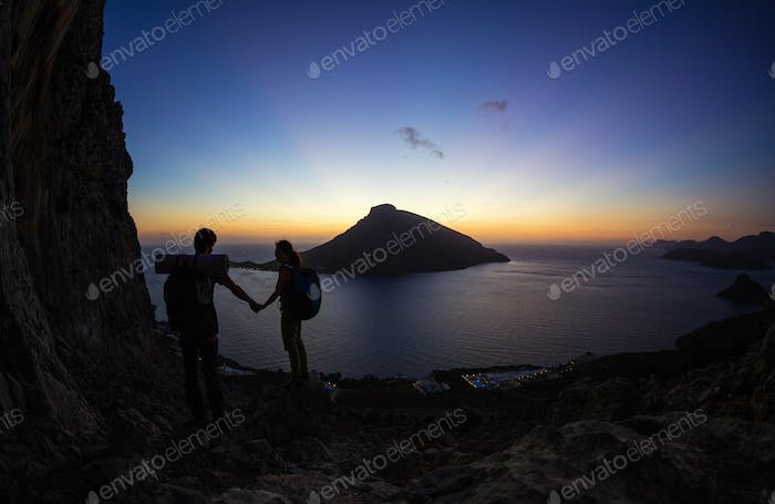 Young couple of rock climbers at sunset