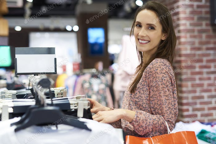 Portrait of smiling woman in the clothes shop