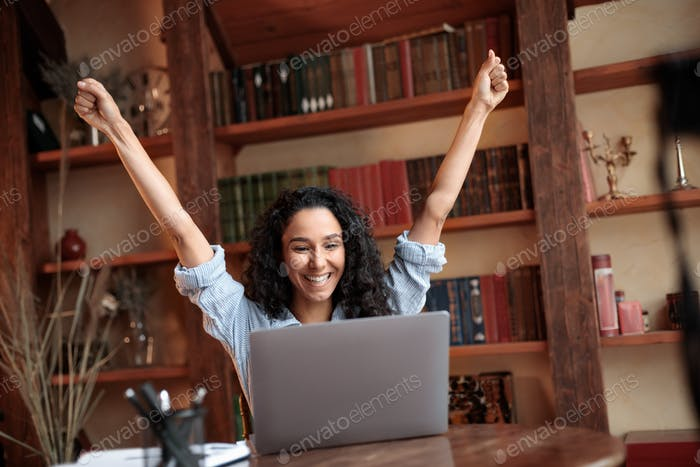 Excited young female feeling ecstatic using laptop