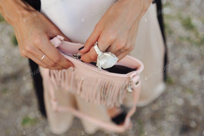 Girl closes her handbag. Close up