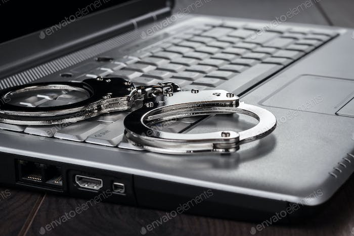 Handcuffs On Laptop Cyber Crime Concept
