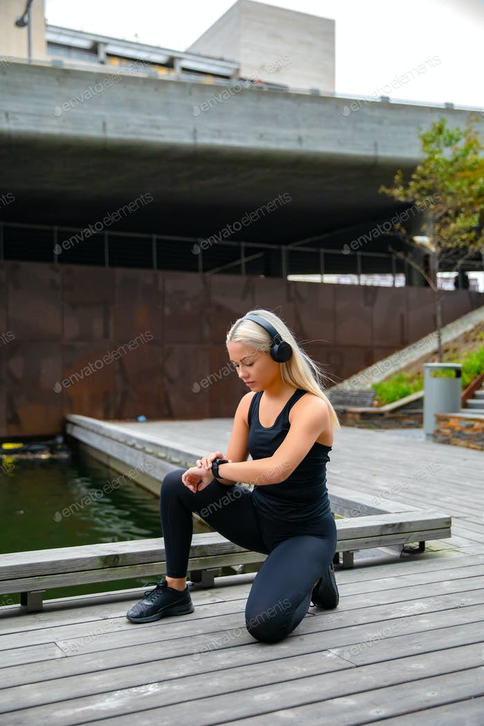 Sporty Woman Listening Music and Using Smartwatch Before Running