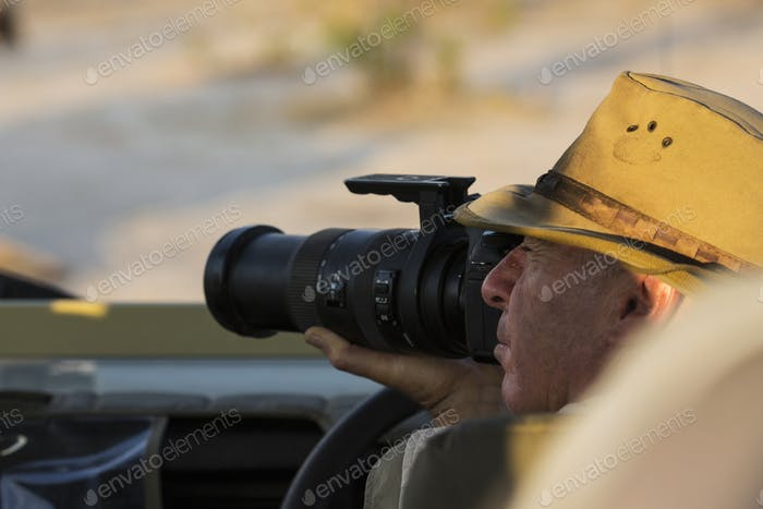 A man in a bush hat using a camera with a long lens.