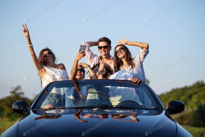 Funny young girls and guys in sunglasses are sitting in a black cabriolet on the road holding their