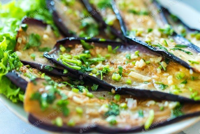 Berenjena frita con ajo en el plato cerca